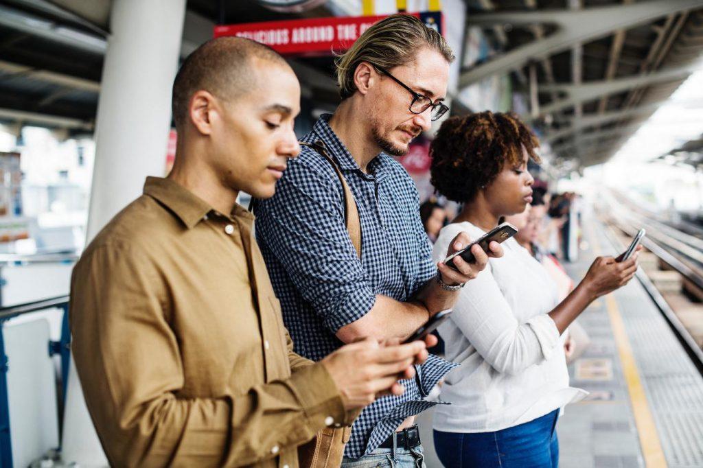 Trois personnes aattendant sur un quai de gare, téléphone à la main - Google Ads